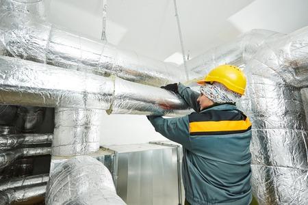 Thermische isolatie. Vrouwelijke isolatie werknemer isoleren van industriële pijp met glaswol en folie