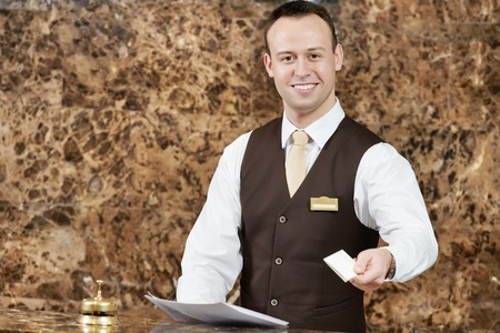 hotel worker: smiling male receptionist passing key card to guest