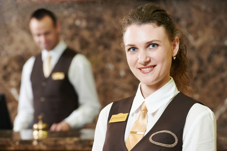 Happy female receptionist worker standing at hotel counter Imagens
