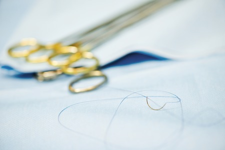 suture: Surgery concept. suture needle and forceps. Shallow DOF. Stock Photo