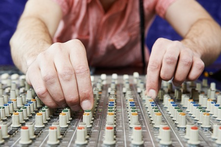 close-up hands of sound engineer work with faders and knobs on professional audio musical mixer photo