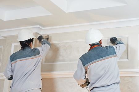 priming: Plasterer at indoor wall renovation stucco decoration with float and plaster