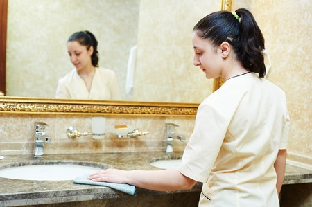 Hotel service. female housekeeping worker cleaning table from dust in bathroom photo