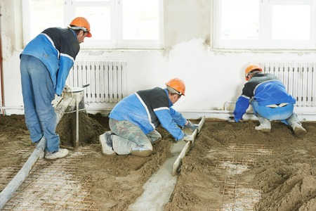 Plasterer workers at indoor concrete cement floor topping with float photo