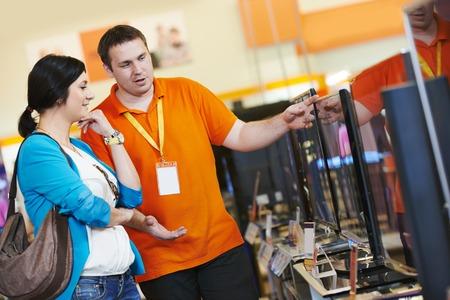 vendedores: Mujer joven tv elegir configurar con asistente de tienda de electrodomésticos en el centro comercial de supermercados