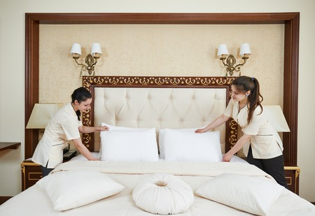 Hotel service. female housekeeping worker maid making bed with bedclothes at inn room photo
