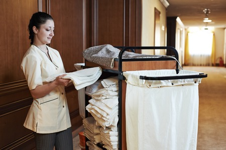 ama de llaves: El servicio de habitaciones del hotel. trabajador de limpieza femenino con ropa de la ropa de cama en el carrito
