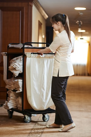 Hotel room service. female housekeeping worker with bedclothes linen in cart photo