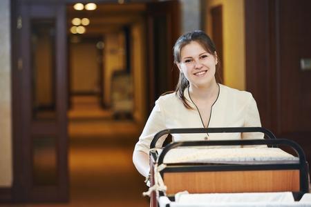 mujer trabajadora: El servicio de habitaciones del hotel. trabajador de limpieza femenino con ropa de la ropa de cama en el carrito