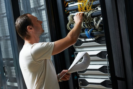 network engineer working in server room photo