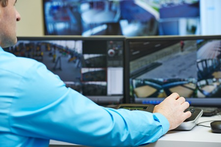 supervisi�n: guardia de seguridad vigilando y operar el sistema de seguridad de vigilancia de vigilancia de video