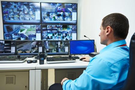 elementos de protecci�n personal: guardia de seguridad viendo el sistema de seguridad de vigilancia de vigilancia de video