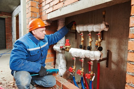 gas fire: repairman engineer of fire engineering system or heating system open the valve equipment in a boiler house