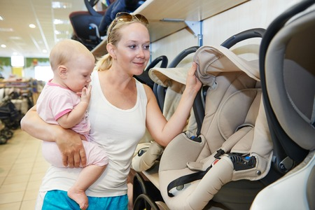 car seat: woman choosing child car seat with little baby in shop supermarket Stock Photo