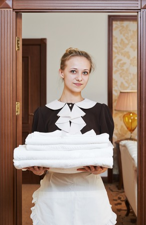 bedclothes: Hotel service. female housekeeping worker with towels and bedclothes at inn room