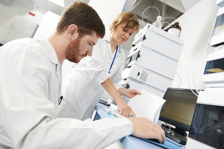 researchers team work at computer scientific analysing data out scientific test in chemistry laboratory photo