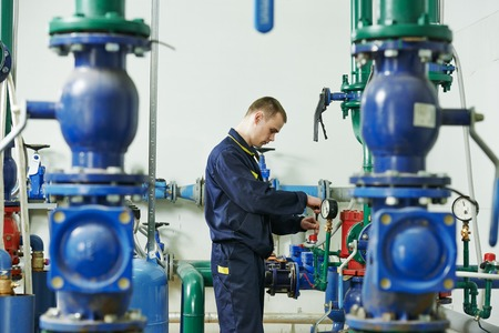 repairman engineer of fire engineering system or heating system open the valve equipment in a boiler house photo