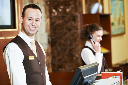 Happy receptionist worker standing at hotel counter Foto de archivo
