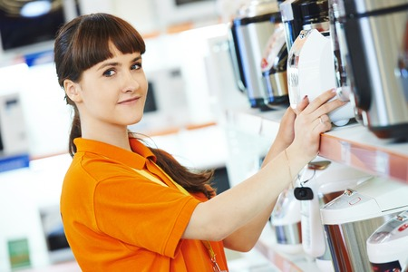 Positive shop assistant in kithenware supermarket store photo