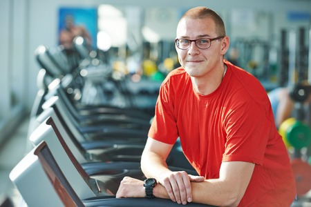 Smiling athlete bodybuilder man in front of barbell weights in fitness gym photo