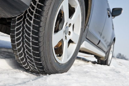 treads: Car with winter tyres installed on light alloy wheels in snowy outdoors road Stock Photo