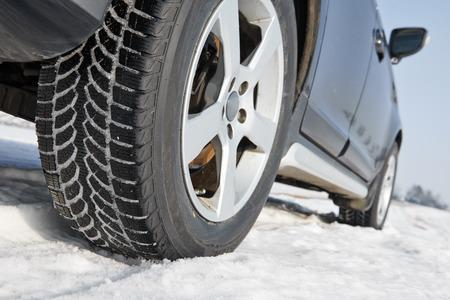 huellas de llantas: Coche con neum�ticos de invierno instalado en llantas de aleaci�n ligera en camino al aire libre cubierto de nieve Foto de archivo