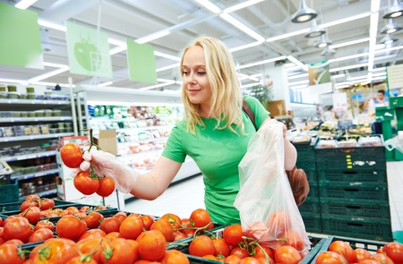 Shopping. Woman choosing bio food fruit tomato in vegetable store or supermarket photo