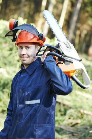 sawyer: Portrait of lumberjack logger worker in protective workwear with chainsaw at forest Stock Photo
