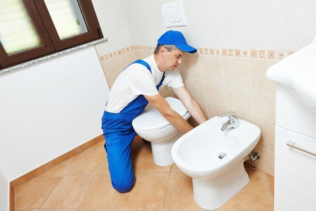 plumber worker working with spanner at sanitary washbasin installation system photo