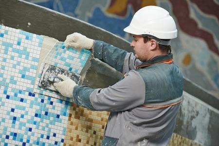 industrial tiler builder worker installing floor tile at repair renovation work photo