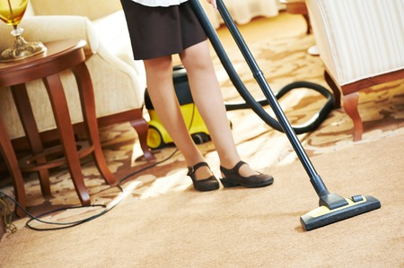 Hotel service. female housekeeping worker with vacuum cleaner in room apartment