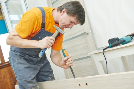 Male carpenter at interior wood door lock installation working with hammer and chisel photo