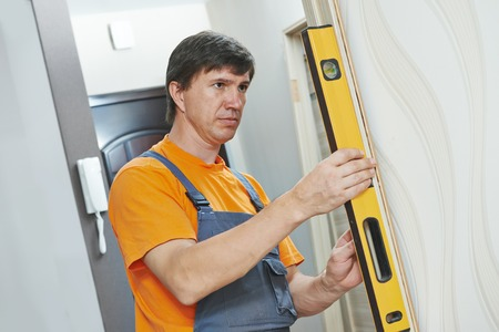 Male carpenter at interior wood door installation working with level photo