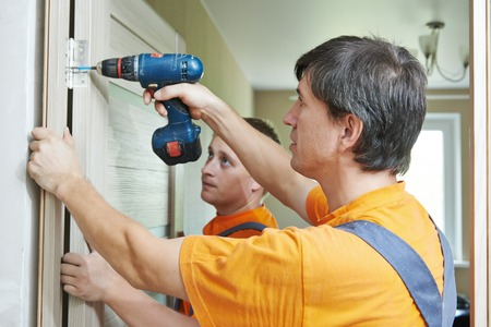 RENOVATE: Two male workers carpenters at internal door installation Stock Photo