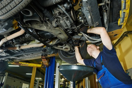 motor mechanic: car garage auto mechanic repairman tighten screw with spanner during automobile maintenance at repair service station Stock Photo
