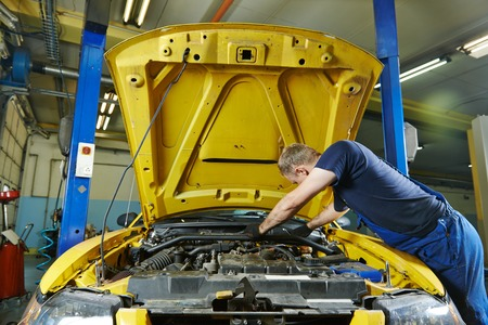 service station: auto mechanic repairman tighten screw with spanner during automobile car maintenance at engine repair service station garage