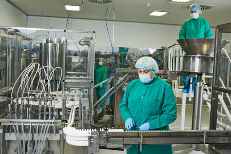 fettler: pharmaceutical factory woman worker operating production line at pharmacy industry manufacture factory Stock Photo