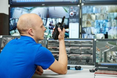 guardia de seguridad: guardia de seguridad de v�deo viendo el sistema de seguridad de vigilancia de monitoreo con el transmisor de radio port�til