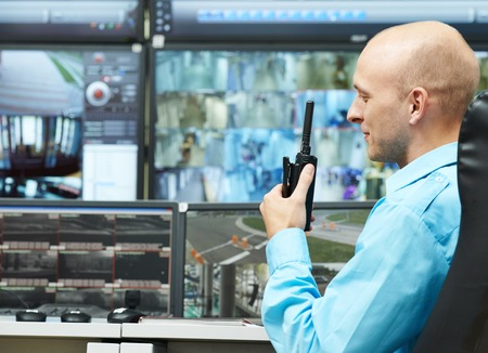 security room: security guard watching video monitoring surveillance security system with portable radio transmitter