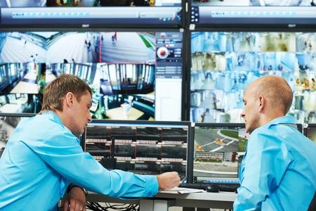 monitoreo: dos guardias de seguridad que miran de vídeo del sistema de vigilancia de seguridad de vigilancia
