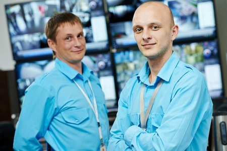 security room: Portraits of two security guards over video monitoring surveillance security system Stock Photo
