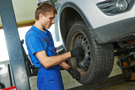 car mechanic screwing or unscrewing car wheel of lifted automobile at repair service station photo