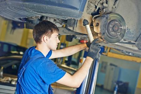 scheduled: garage auto mechanic repairman checking car brake during automobile maintenance at repair service station