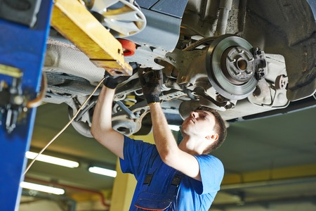 scheduled: garage auto mechanic repairman checking car suspension during automobile maintenance at repair service station Stock Photo