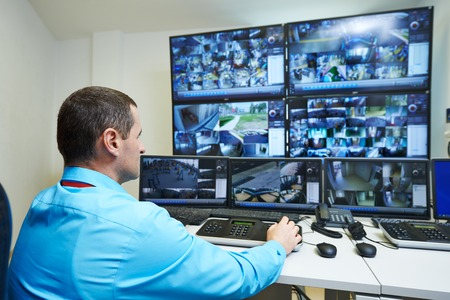 video surveillance: security guard watching video monitoring surveillance security system Stock Photo