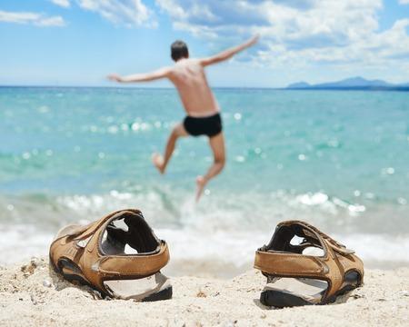 sandalias: concepto de vacaciones. hombre saltando en el mar tropical torquoise en las vacaciones Foto de archivo
