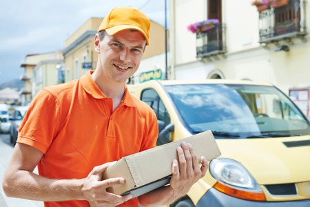 Smiling male postal delivery courier man outdoors  in front of cargo van delivering package photo