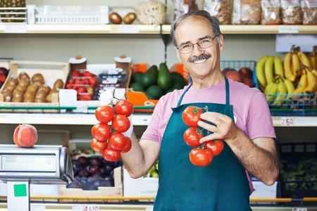 italian man: adult senior sale man with tomato at vegetable market shopping store