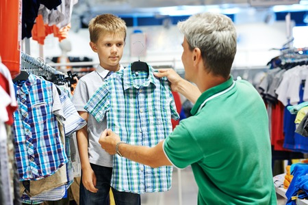 children's wear: man father choosing shirt with son boy during shopping at garments shop Stock Photo