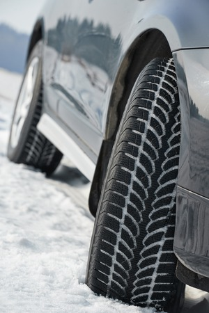 Car with winter tyres installed on light alloy wheels in snowy outdoors road Stock Photo